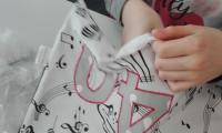 Uczennica klasy 8 wykonuje poduszkę dla zespołu Dżem