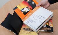 """Zestaw gadżetów z filmu """"Excentrycy, czyli po słonecznej stronie ulicy"""": płyta z muzyką filmową, książka z autografami oraz plakat promocyjny, fot. Andrzej Goiński"""